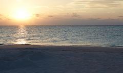 Sun Setting Over Beautiful Deserted Beach Stock Photos