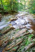 slippery rocks in a mountain stream - stock photo