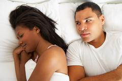 couple in bed with relationship difficulties - stock photo