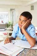 Fed up boy doing homework in kitchen Stock Photos