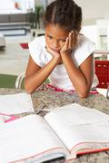 Fed up girl doing homework in kitchen Stock Photos