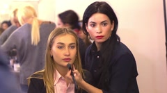 Makeup artist paints a pretty model before the show behind the scenes Stock Footage