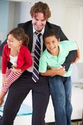 Children greeting father on return from work Stock Photos