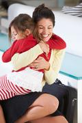 daughter greets mother on return from work - stock photo