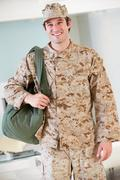 Male soldier with kit bag home for leave Stock Photos