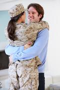 Husband greeting military wife home on leave Stock Photos