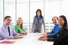 Businesswoman conducting meeting in boardroom Stock Photos
