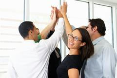 Business team giving one another high five Kuvituskuvat