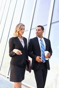 Businesspeople with takeaway coffee outside office Stock Photos
