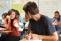 Students passing notes in class Stock Photos
