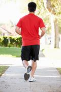 Rear view of male runner exercising on suburban street Stock Photos