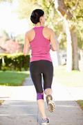 Rear view of female runner exercising on suburban street Stock Photos