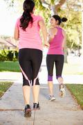 Rear view of two female runners on suburban street Stock Photos