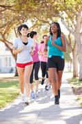 Group of female runners exercising on suburban street Stock Photos