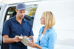 Customer signing for delivery from courier Stock Photos