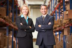 Businesswoman and businessman in distribution warehouse Stock Photos