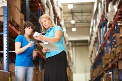 Businesswoman and female worker in distribution warehouse Stock Photos