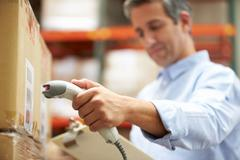 Worker scanning package in warehouse Stock Photos