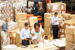 Workers in warehouse preparing goods for dispatch Stock Photos