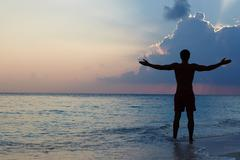 Silhouette of man with outstretched arms on beach at sunset Stock Photos