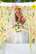 bride sitting under decorated canopy at wedding - stock photo