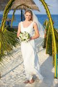 Beautiful bride getting married in beach ceremony Stock Photos