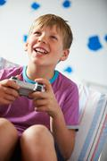 Boy holding controller playing video game Stock Photos