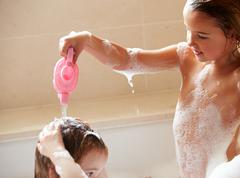 Two girls sharing bubble bath and washing hair Stock Photos