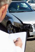 Loss Adjuster Inspecting Car Involved In Accident Stock Photos