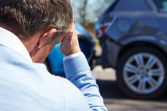 Stressed Driver Sitting At Roadside After Traffic Accident - stock photo