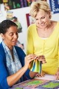 Two women sewing quilt together Stock Photos