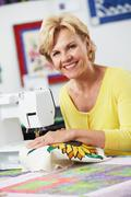 Portrait of woman using electric sewing machine Stock Photos