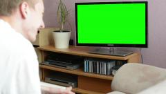 Man watches TV(television) - green screen - man laughs Stock Footage