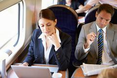 Businesswoman commuting to work on train and using laptop Stock Photos