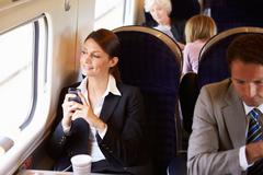 Businesswoman commuting to work on train using mobile phone Stock Photos