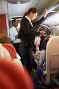 Businesswoman using mobile phone on busy commuter train Stock Photos