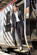 Businesswoman getting off train at platform Stock Photos