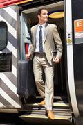 Businessman getting off train at platform Stock Photos