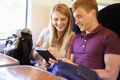 young couple reading e book on train journey - stock photo