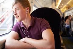 young man listening to music on train journey - stock photo