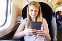 teenage girl reading e book on train journey - stock photo