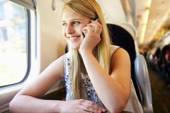 Teenage girl using mobile phone on train journey Stock Photos