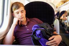 Young man resting on train journey Stock Photos