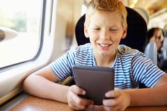boy reading e book on train journey - stock photo
