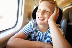 boy relaxing on train journey - stock photo