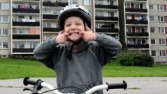 child (a little boy) grimaces - child with bike - house in background - stock footage