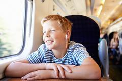 boy listening to music on train journey - stock photo