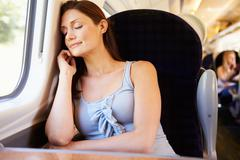 woman resting on train journey - stock photo