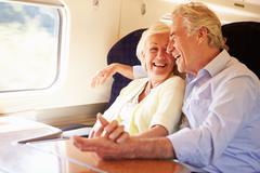 Senior couple relaxing on train journey Stock Photos