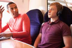 Young man disturbing train passengers with loud music Stock Photos